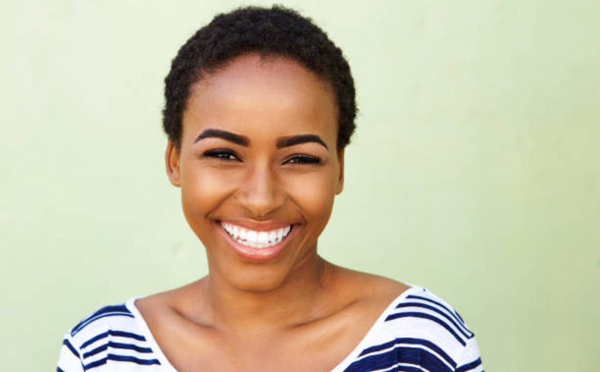 Close up portrait of young black woman smiling against green wall